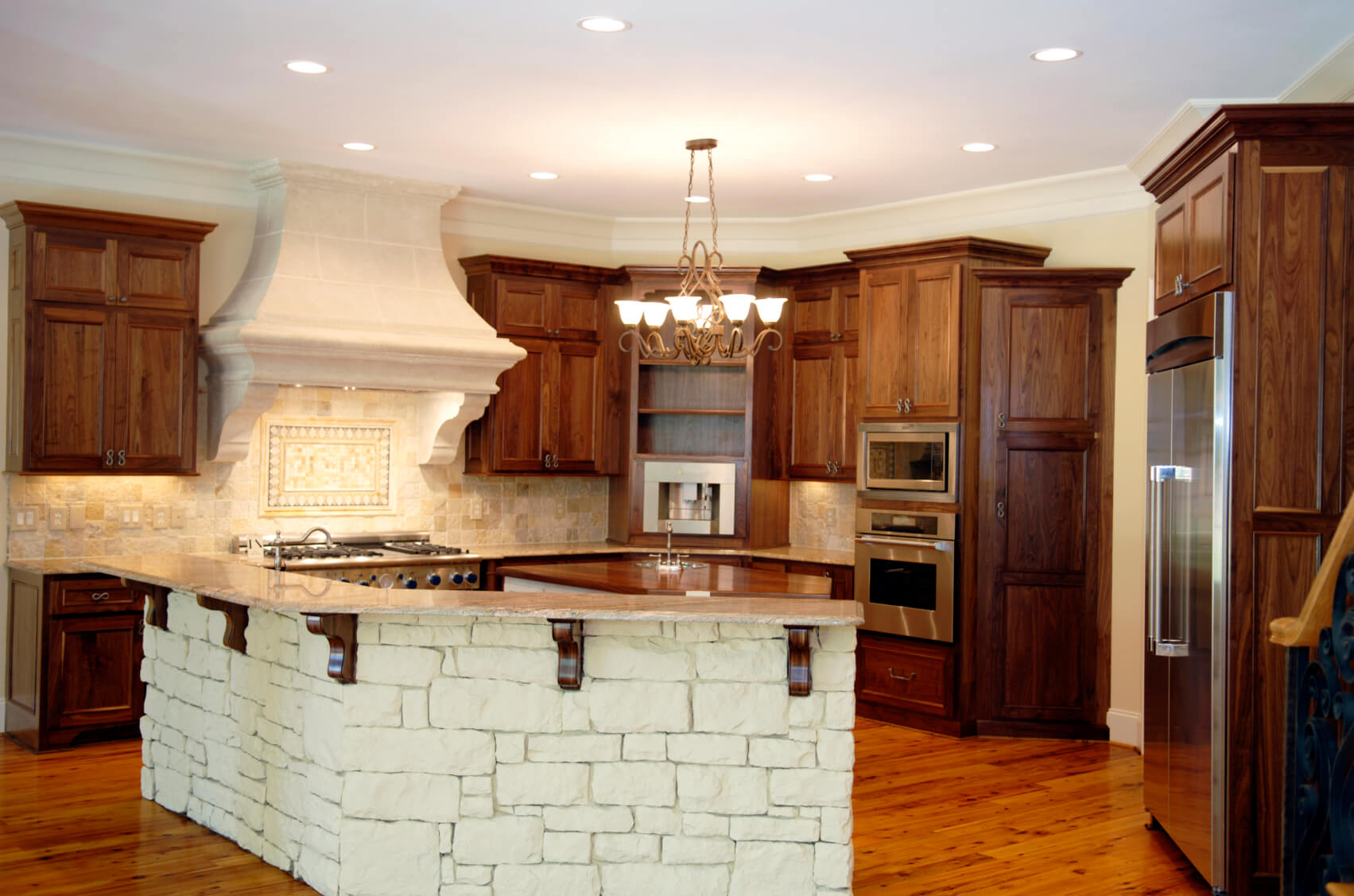 Unique, white stone island with marble countertop stands apart in this kitchen flush with natural wood tones.