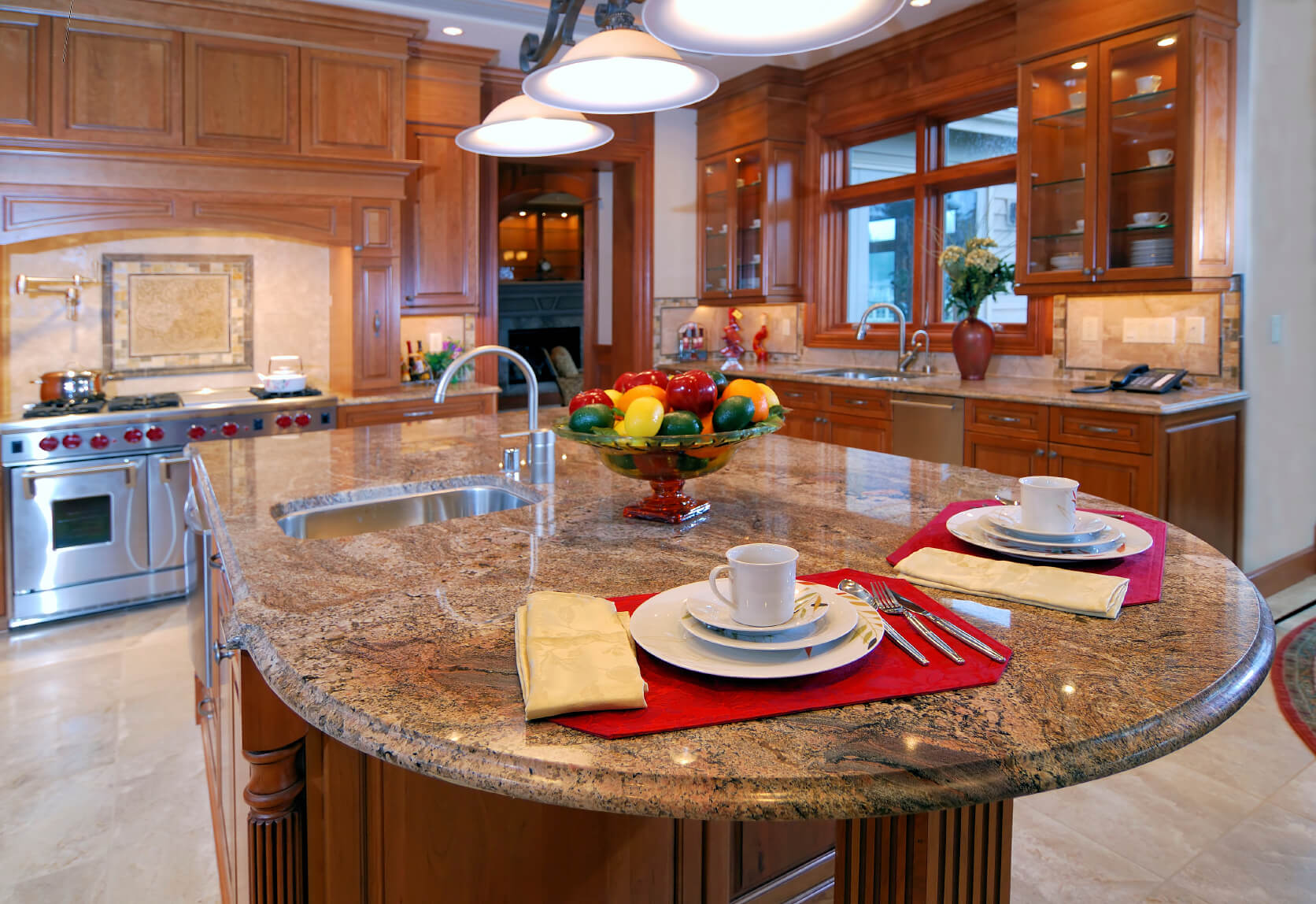 Rich patterned marble countertop extends to round dining space on this natural wood island.