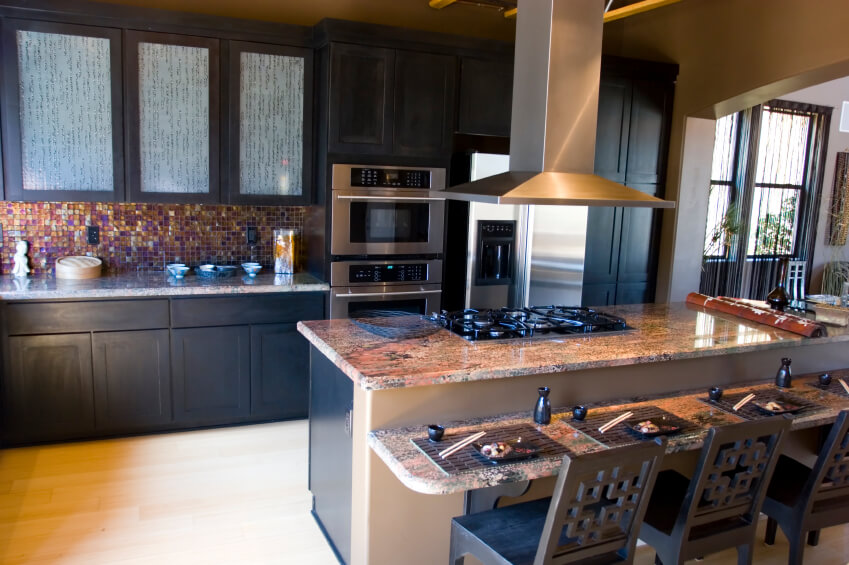 Black Painted Wood Cupboards Surround Multi Colored Mosaic Tile Backsplash  And Salmon Toned Marble Countertops