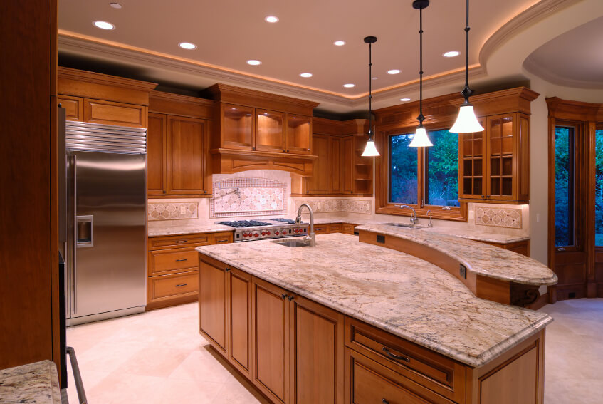 Array of recessed lighting in the raised ceiling of this kitchen highlight large two-tiered marble countertop island with natural wood cabinetry all around.