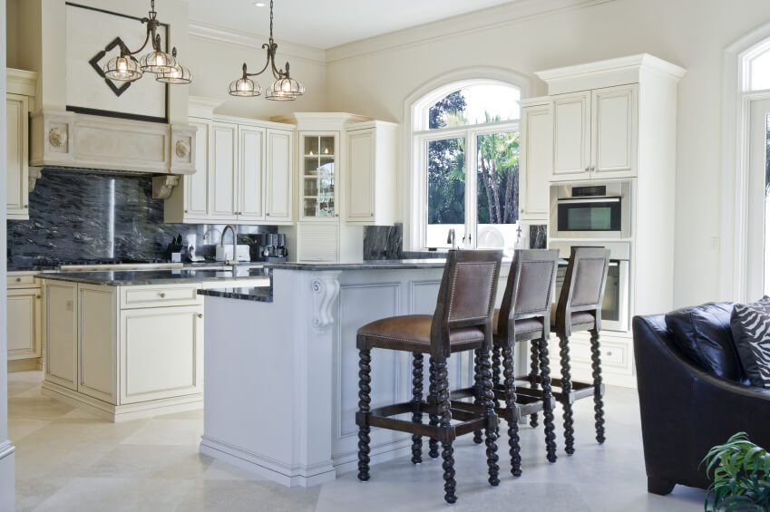 White kitchen features dual islands: traditional model featuring sink and dark blue marble countertop, and second dining-area island with space for three.