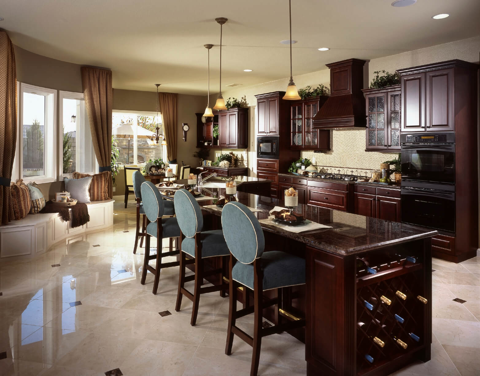 Dark cherry wood and darker marble countertops unify this kitchen, featuring expansive L-shaped island with built-in wine rack and ample dining space.