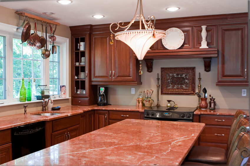 Warm Pink Marble Countertops In This Kitchen Pair With Stained Wood  Cabinetry In This Cozy Kitchen