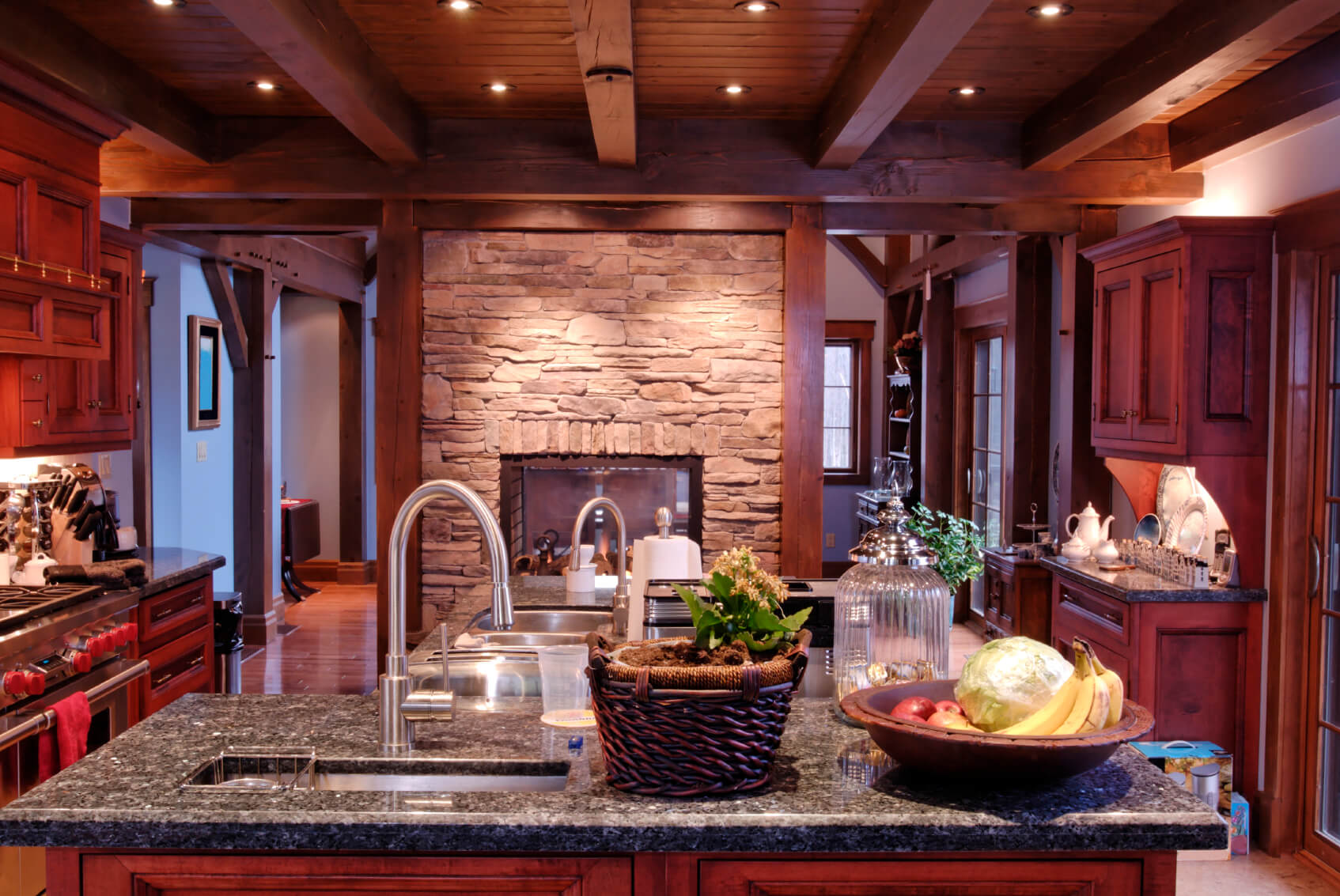 Here we see the prior rustic look kitchen at night time, with embedded light highlighting cherry wood tones.