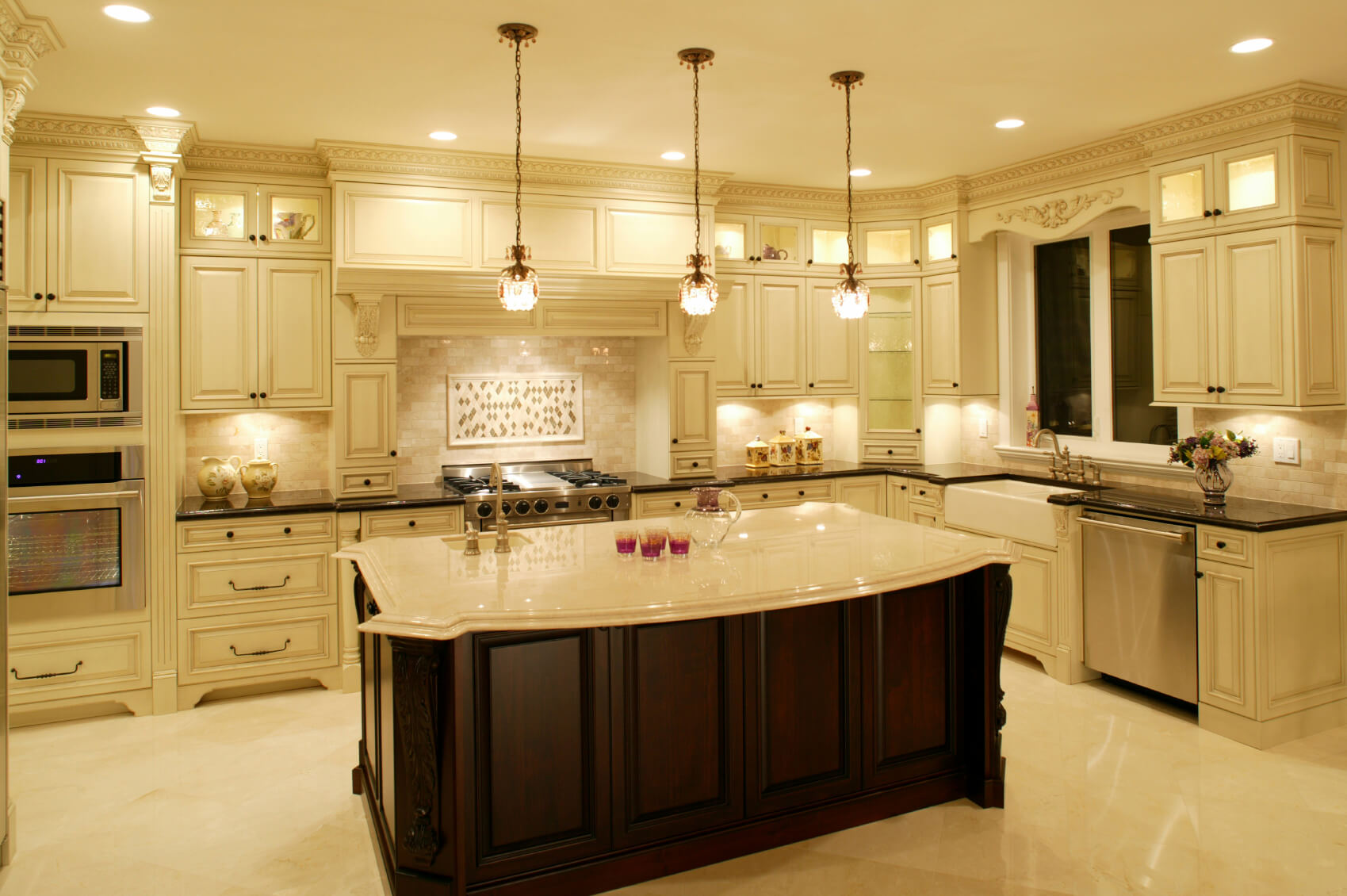 Luxurious Kitchen Awash In Light Marble Tones, Dominated By Large Dark Wood  Island With Filigreed