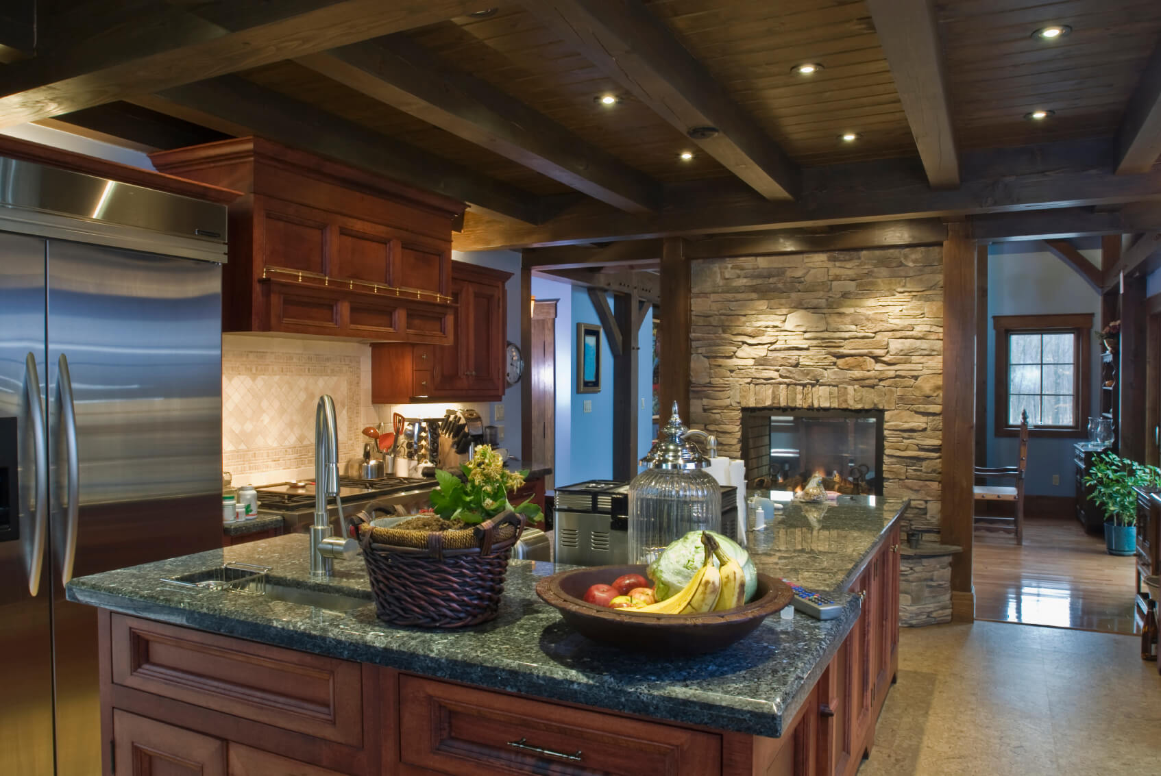 Rustic look kitchen features brick pass-through fireplace under dark wood exposed beams, with cherry wood cabinetry and forrest green marble countertops.