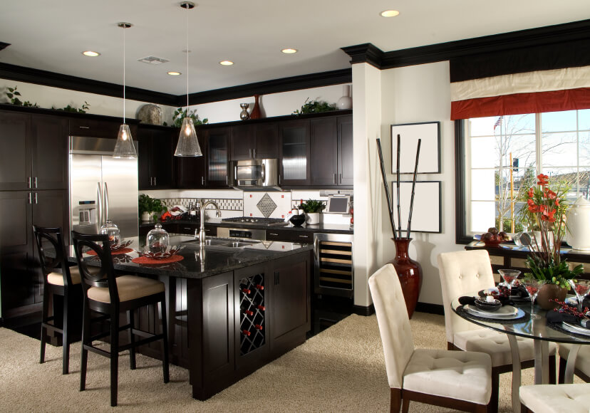 Les murs blancs contrastés et le design en bois teinté sombre de cette cuisine ouverte séparent visuellement l'espace de la salle à manger.