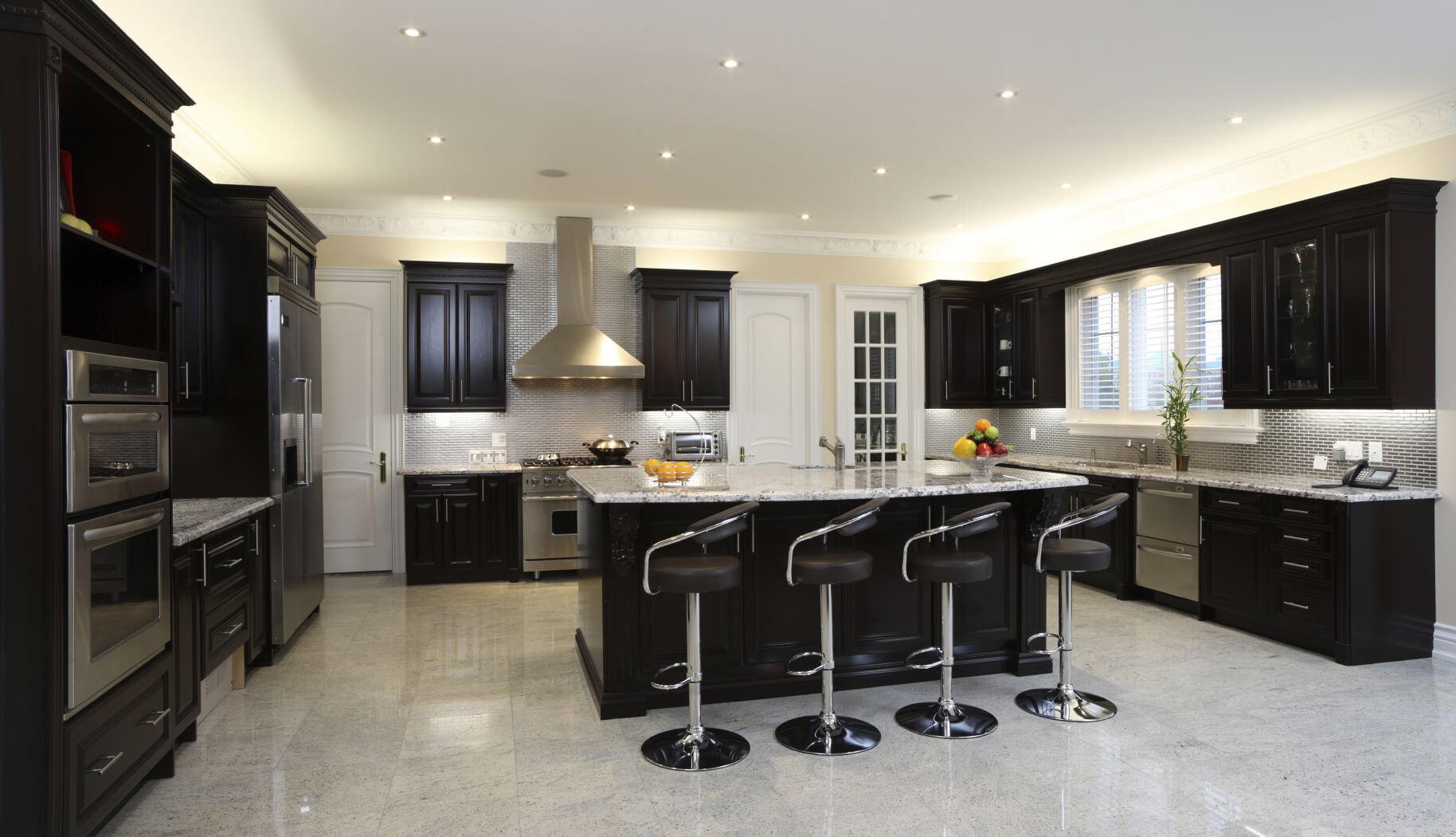 Spacious modern kitchen with dark cabinetry breakfast bar 4 modern diner style stools and