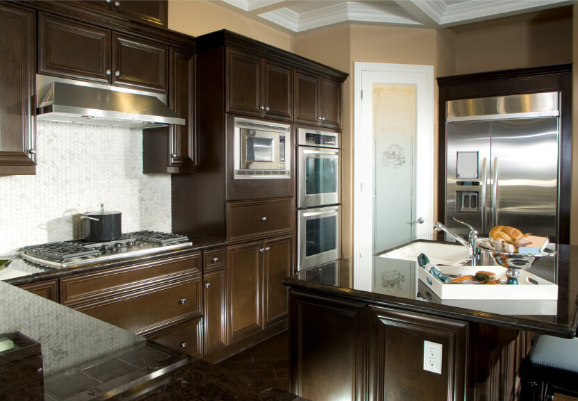 Dark Chocolate Wood Cabinetry Surrounds White Tile Backsplash Over Dark  Tile Flooring In This Cozy Kitchen