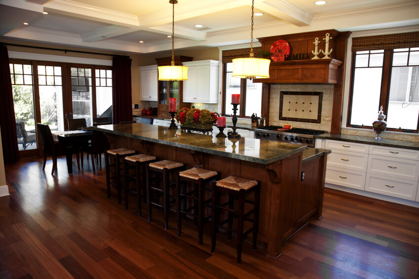 Rich dark wood tones throughout this kitchen featuring two-tier island with full bar seating and dark marble countertops.