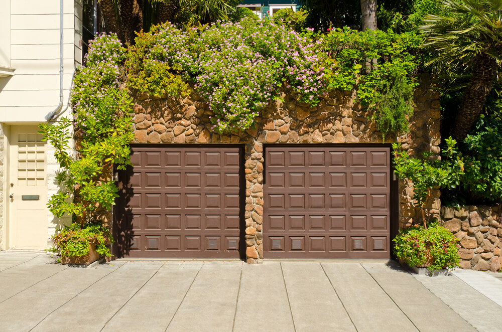 This stone facade garage is nearly hidden beneath vegetation, with brown square paneled doors.