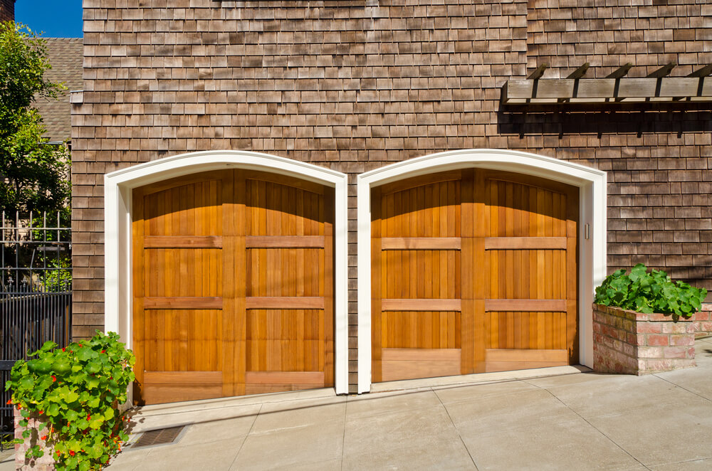 This side-facing garage features two light natural wood doors in arched, white frame. Custom shape accommodates sloped driveway.