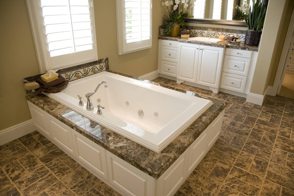 Wide Expanse Of Brown Tile Flooring Matches The Marble Topped Soaking Tub  Enclosure In This Bathroom