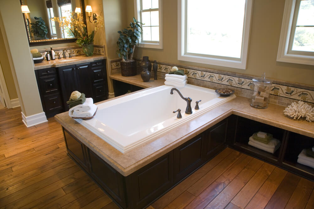 Natural hardwood flooring beneath rich, dark stained wood cabinetry surrounds this rectangular soaking tub in beige marble enclosure. Surface extends along wall to provide shelving and countertop space beneath windows.