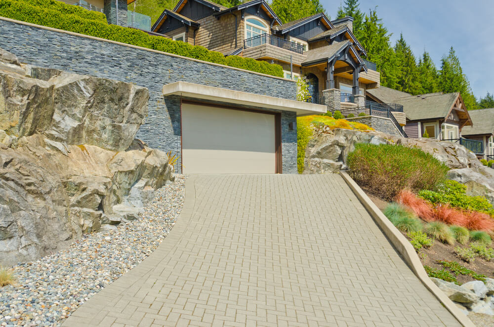 Discreet single door garage sits under hedge rows, surrounded by large stones in this home. Flat concrete overhang provides shade for beige toned door.