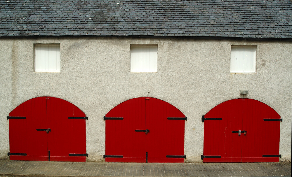 Bold red painted carriage style doors adorn this three stall garage under stucco walls.