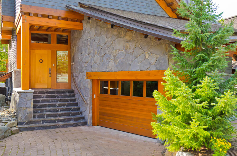 Stone facade home features bright toned natural wood throughout structure, including side facing garage door and frame, with large upper panel windows.