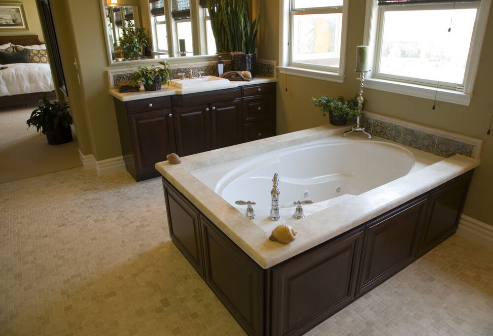 In a bathroom featuring patterned beige tile flooring and dark wood cabinetry, this oval soaking tub with whirlpool jets sits inside raised-surface enclosure, with detail tile patterns against exterior wall.
