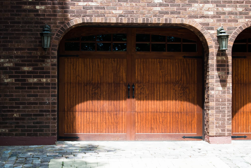 Arched brick design frames this two car garage with carriage style doors in natural warm wood tones, featuring upper panel wide window design.
