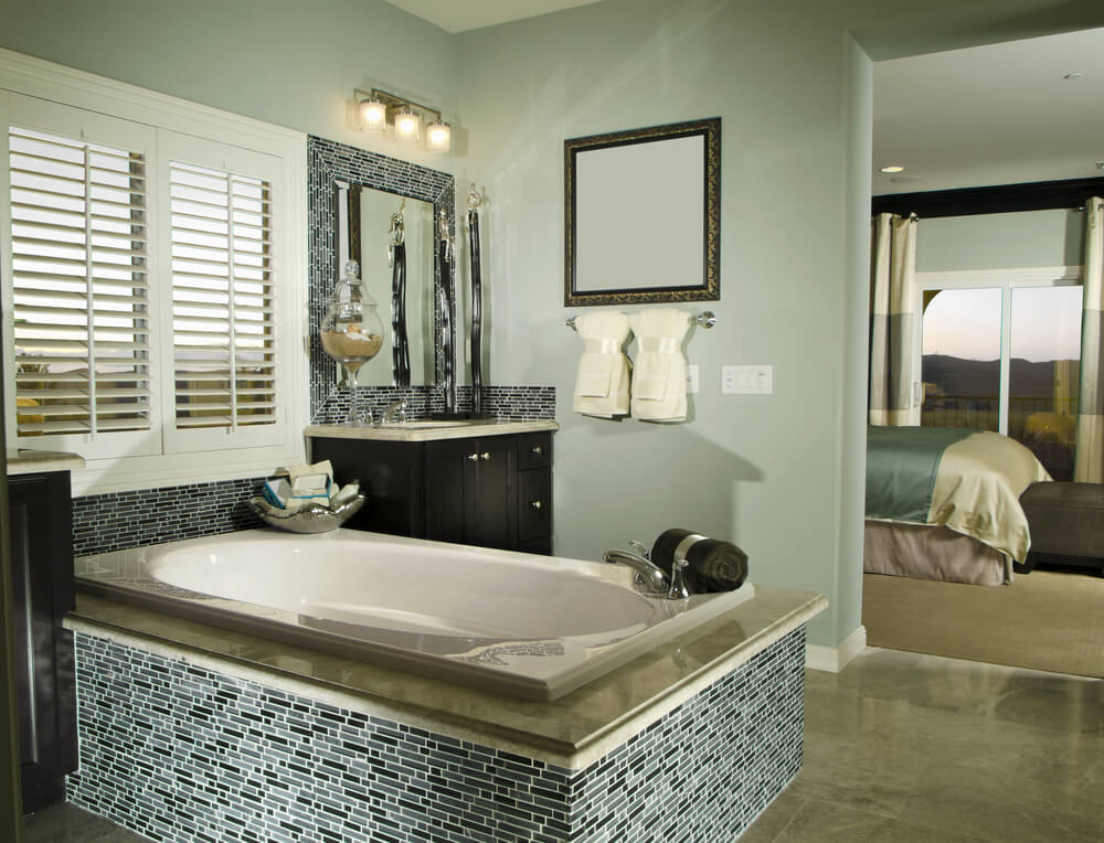 Oval soaking tub with chrome corner faucet is seated inside patterned tile enclosure between twin dark wood vanities over dark marble flooring in this luxury bathroom.