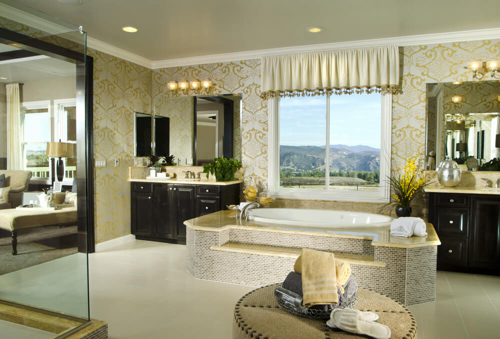 Luxury master bathroom with large step-up soaking tub in the center between two vanities