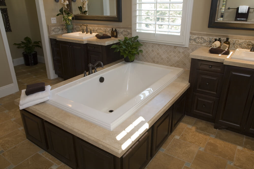 Here's a similar tub, with squared edges and side mounted faucet. Beige marble top contrasts with white tub over dark wood panel enclosure. Darker beige tile flooring surrounds matching dark wood vanities.