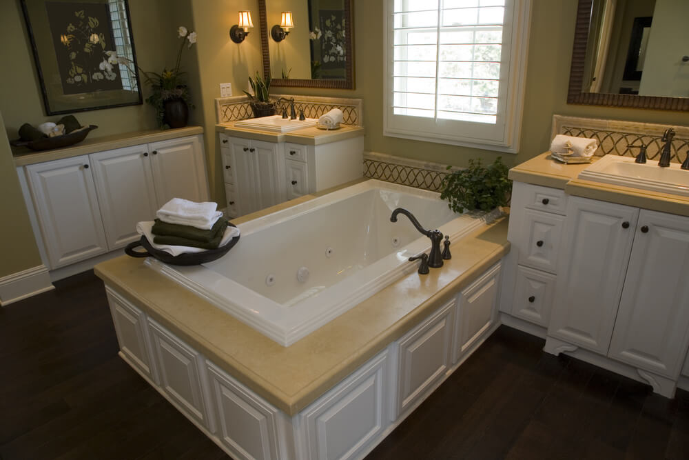 Beige marble countertops on the twin vanities match the soaking tub enclosure over white wood paneling in this bathroom, featuring dark natural wood flooring.