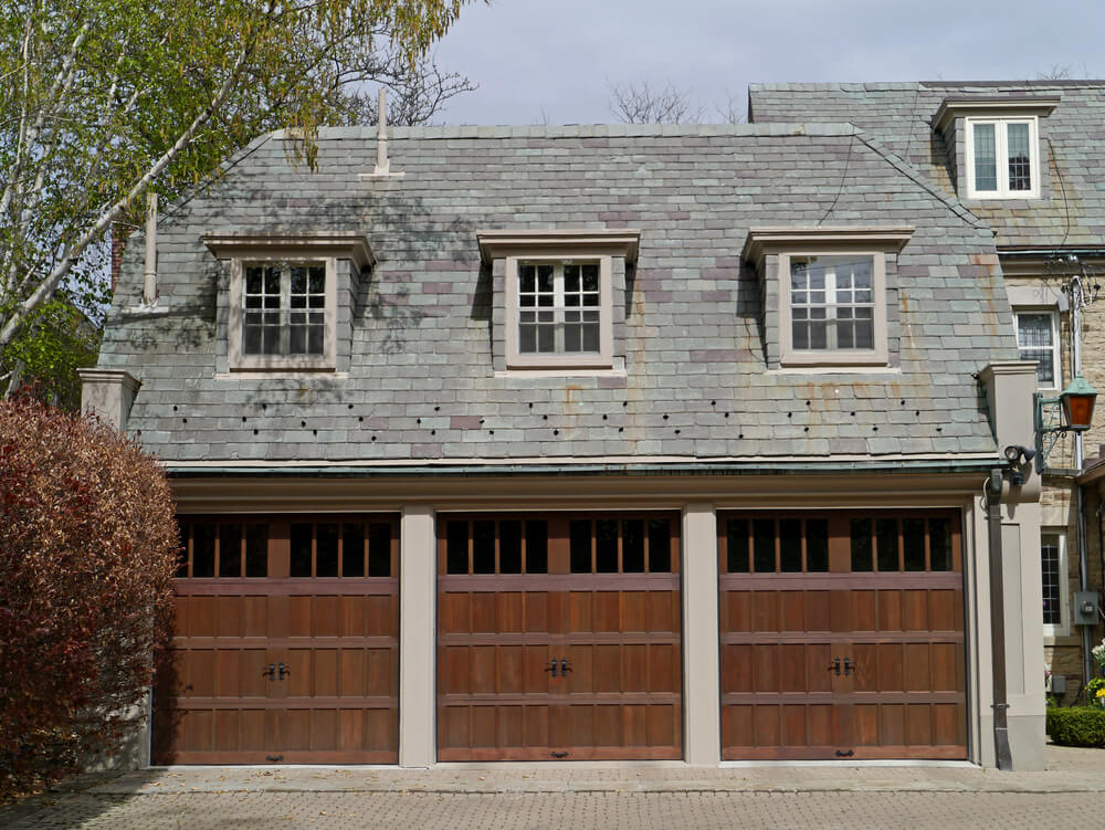 This front-extension three car garage features carriage style dark natural wood doors with upper panel slot windows.
