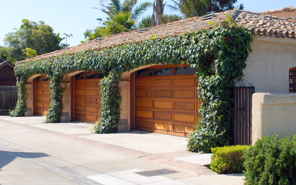 Side-facing garage frames three natural wood doors in ivy-covered adobe facade.