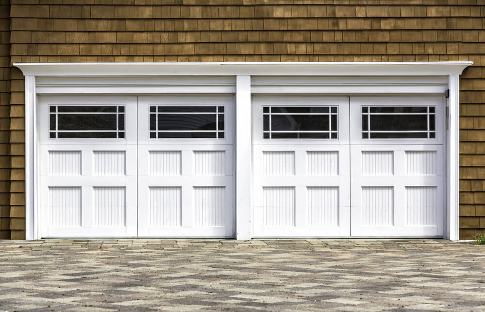 Natural wood shingle siding surrounds this two car garage in white painted wood, featuring large upper panel window design.