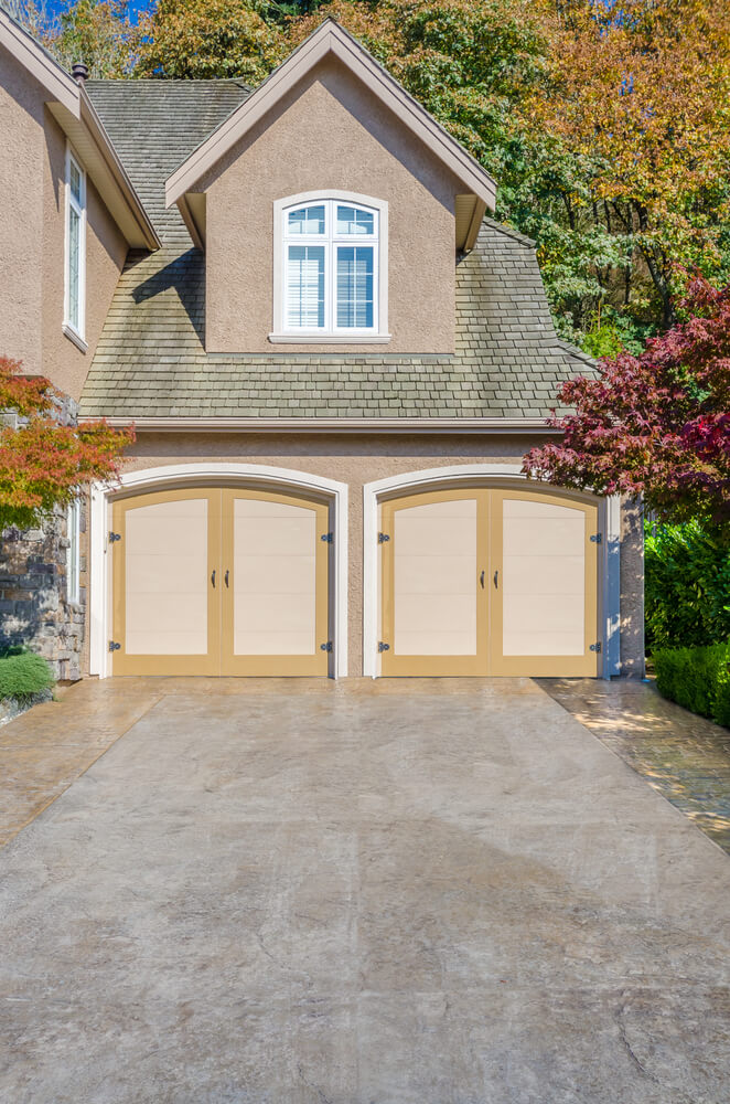 Here we have an attached, front facing two car garage, with carriage-style doors painted beige and yellow, framed in white wood on a stucco wall.