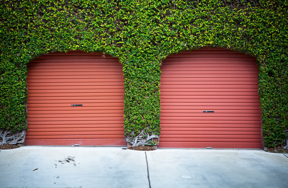 Two red aluminum garage doors on this home are framed in ivy facade for unique, bold look.