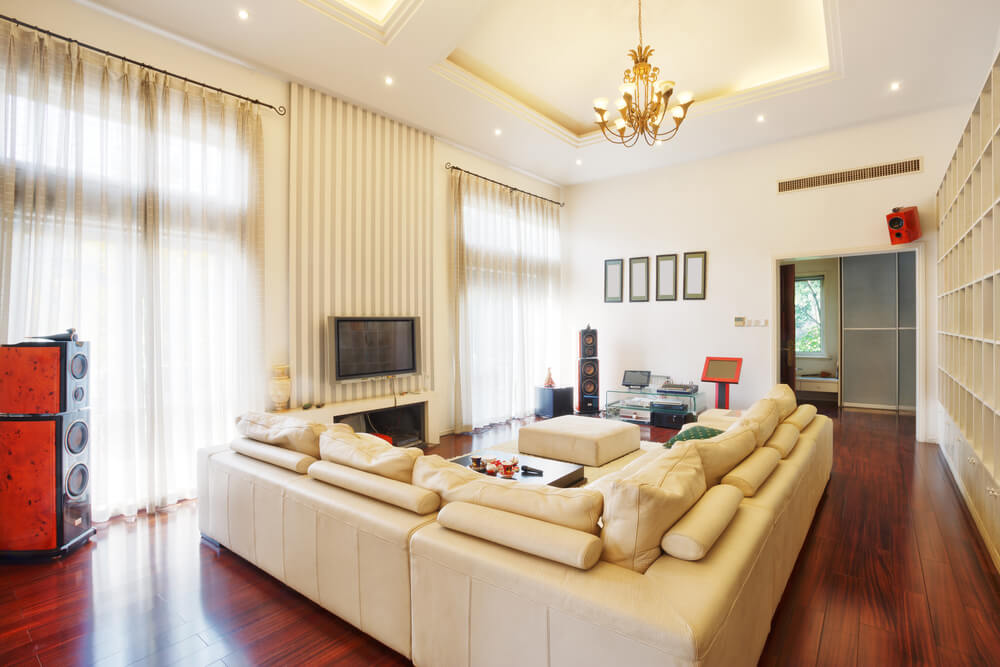 Cherry wood flooring supports large beige leather living room sectional sofa in this high ceiling space, with floor to ceiling windows facing equal height shelving under detailed ceiling with gold chandelier.