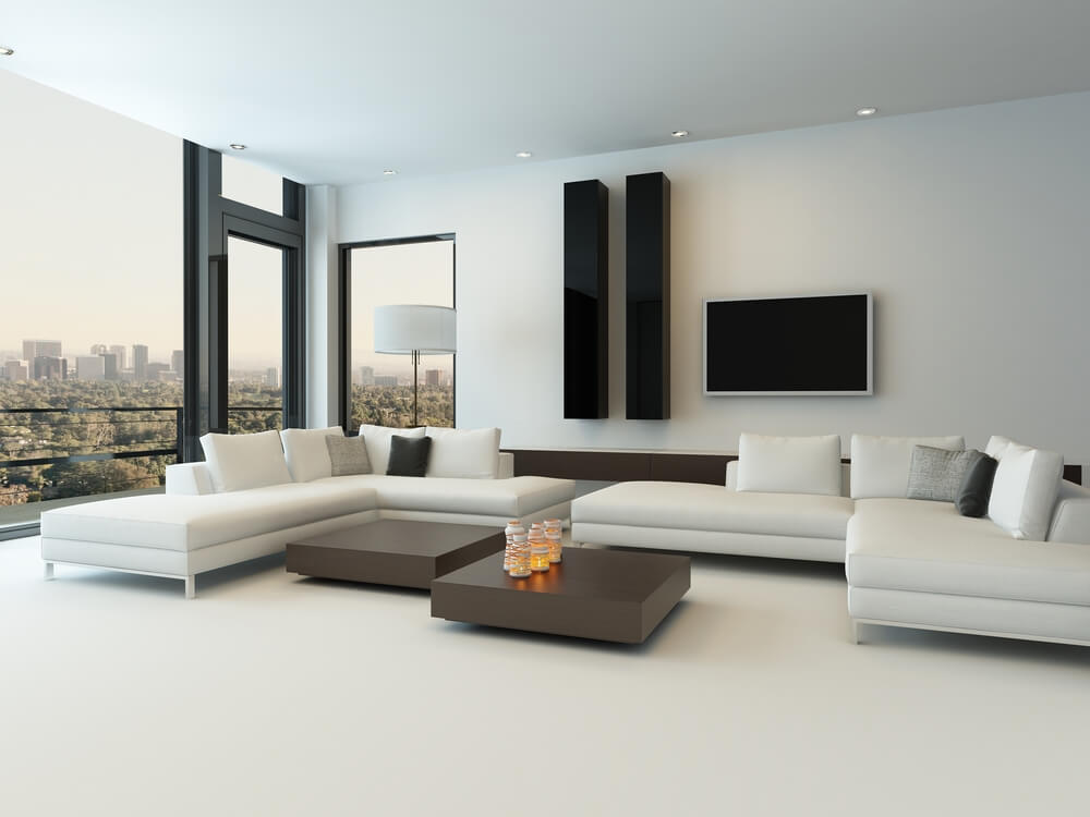 Dual living room sectional sofas pair up in this white space, with pillow backs and chaise features, around flat grey coffee tables and minimalist decoration.