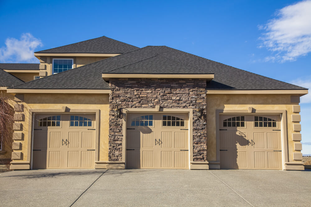Front-extension garage here features unique design with stone facade surrounding central stall. Light brown painted carriage style wood doors feature upper-panel windows.