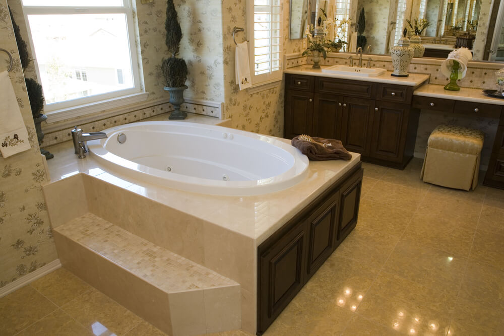 This soaking tub employs a whirlpool system, for a massaging experience. With marble, tile, and dark wood panel enclosure, this unit sits against a large window for comfort and sunlight.