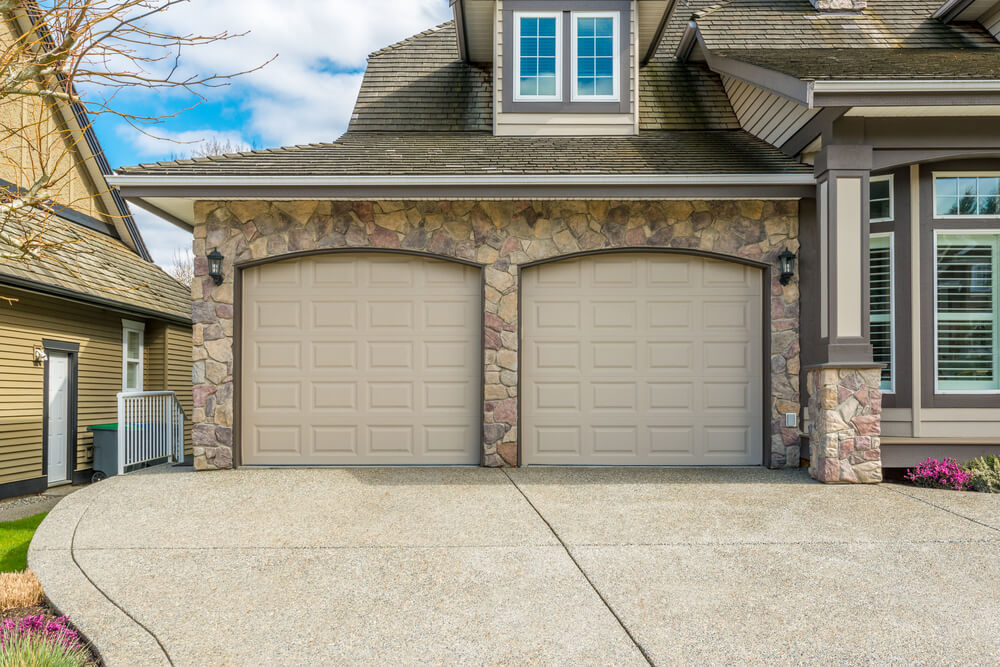 Attached, front facing garage with stone facade features two light-brown aluminum doors seated between black sconce lighting.