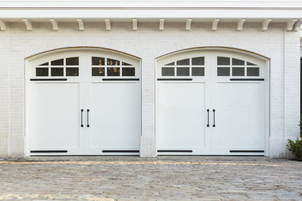 This bright white brick home features two car garage with white painted wood carriage style doors in arched brick frame.