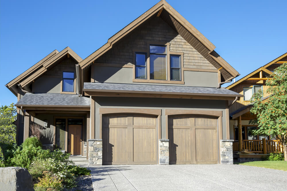 Predominantly brown home featuring two car front-extension garage, with natural wood doors matching the home's framing, sandwiched between lower stone walls.