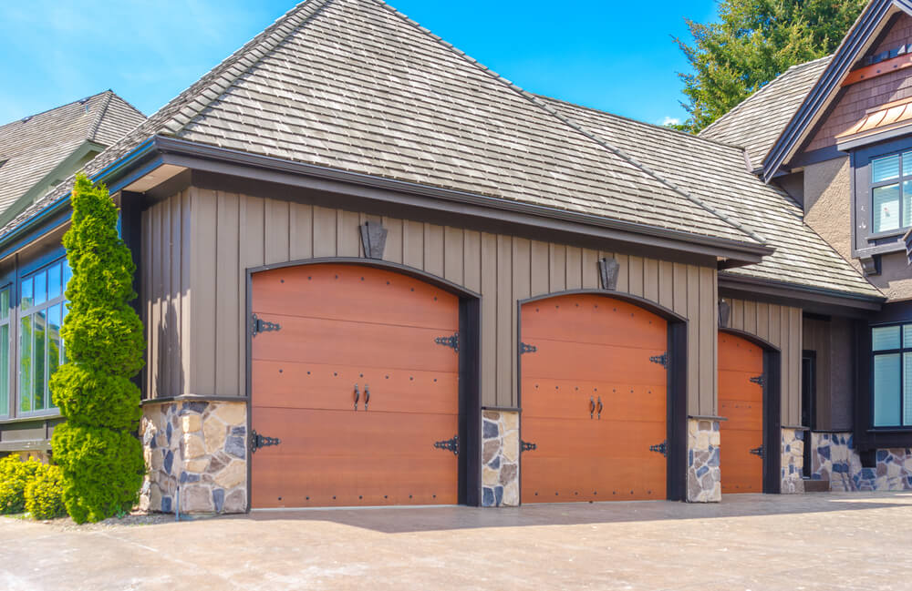 This side facing three car garage features bright natural wood carriage style doors, framed in black, with lower level stone facade wall.