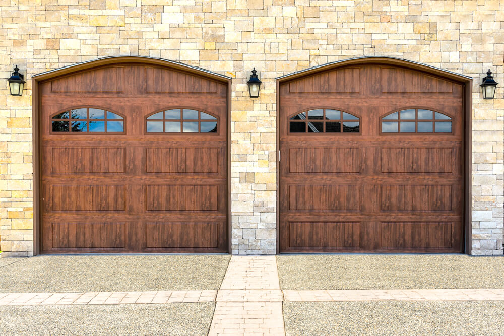 Stone brick home featuring two car dark wood garage doors with 3/4 height window panels.