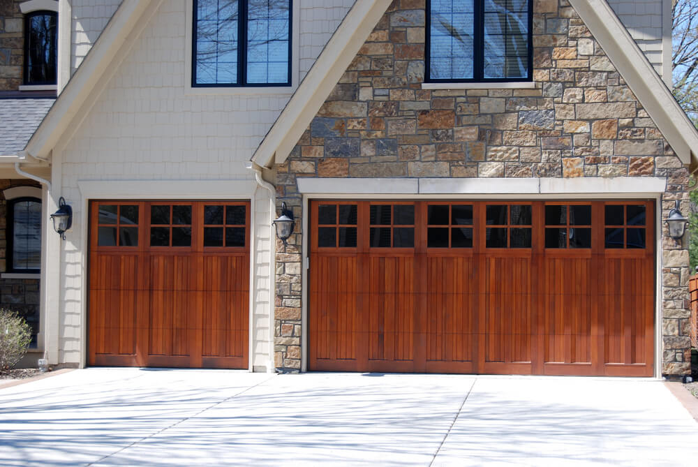 Three car, front facing attached garage splits stalls into two doors, with single car on left and double-stall on right. Doors are rich natural wood with upper panel windows.