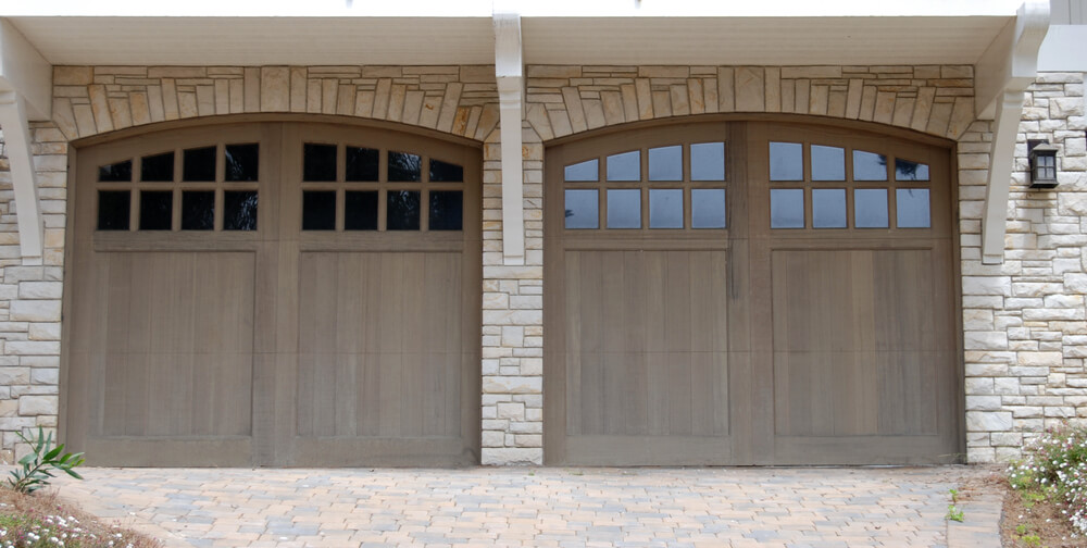 Two car garage features natural wood arched doors with upper panel windows, nestled in light stone brick facade beneath white wood overhang.