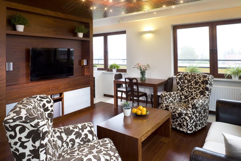 Un autre petit salon avec des fauteuils à motifs noirs et blancs encadre un canapé causeuse avec une table basse rectangulaire en bois.  Cette pièce pourrait être utilisée comme salon ou chambre familiale.