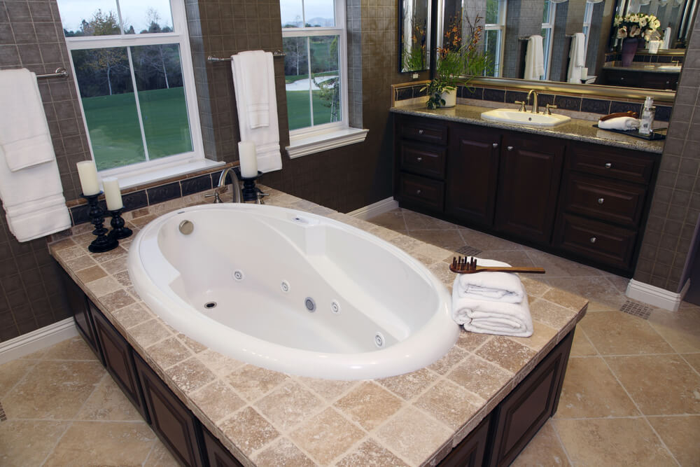 This luxurious bathroom features contrasting tones of dark wood cabinetry and light tile flooring and bathtub enclosure. Whirlpool jets in this oval soaking tub add massage feature, while adjacent windows afford relaxing view outdoors.