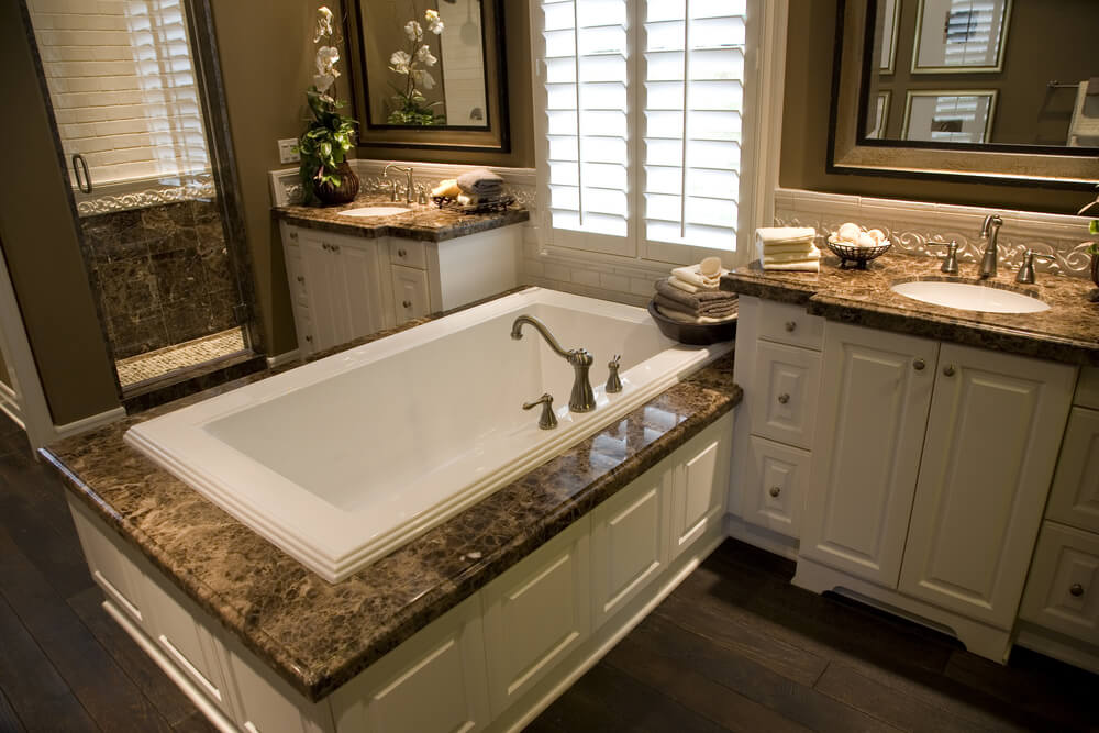 Dark marble countertops over white wood cabinetry match the twin vanities with this soaking tub enclosure over dark stained natural hardwood flooring. Luxurious bathroom features glass door shower to the left.