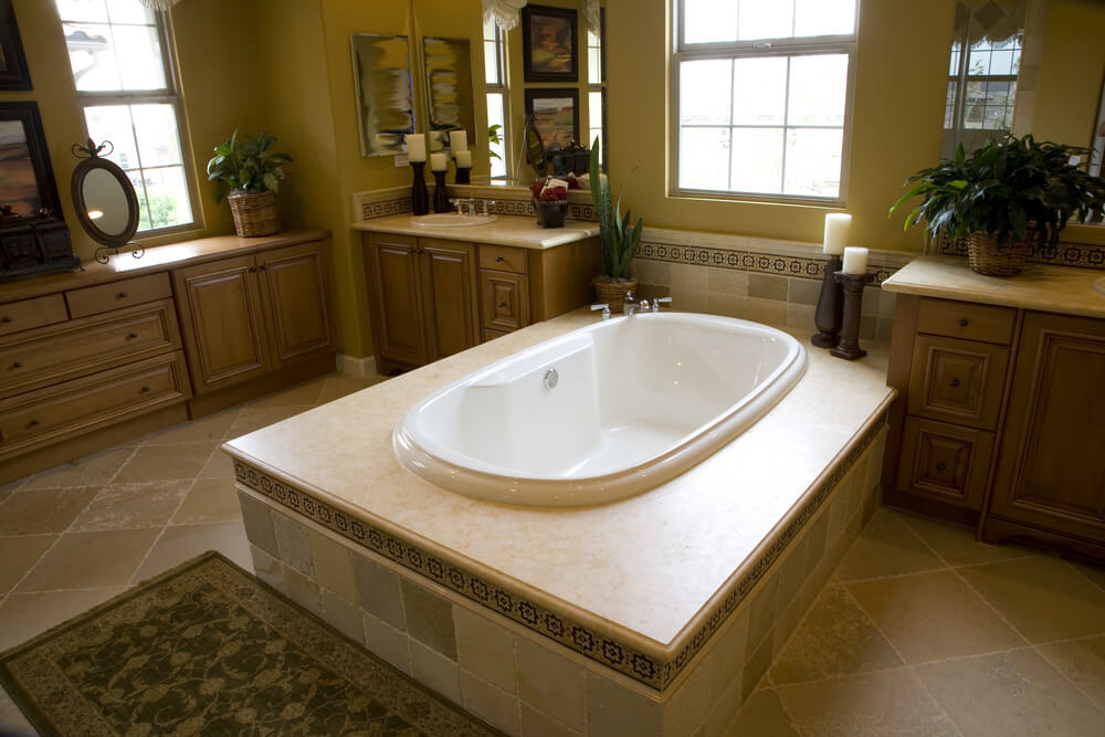 White oval soaking tub in this bathroom sits at center of enormous tile enclosure, between twin natural wood vanities. Windows all around provide natural light over the beige tile flooring.