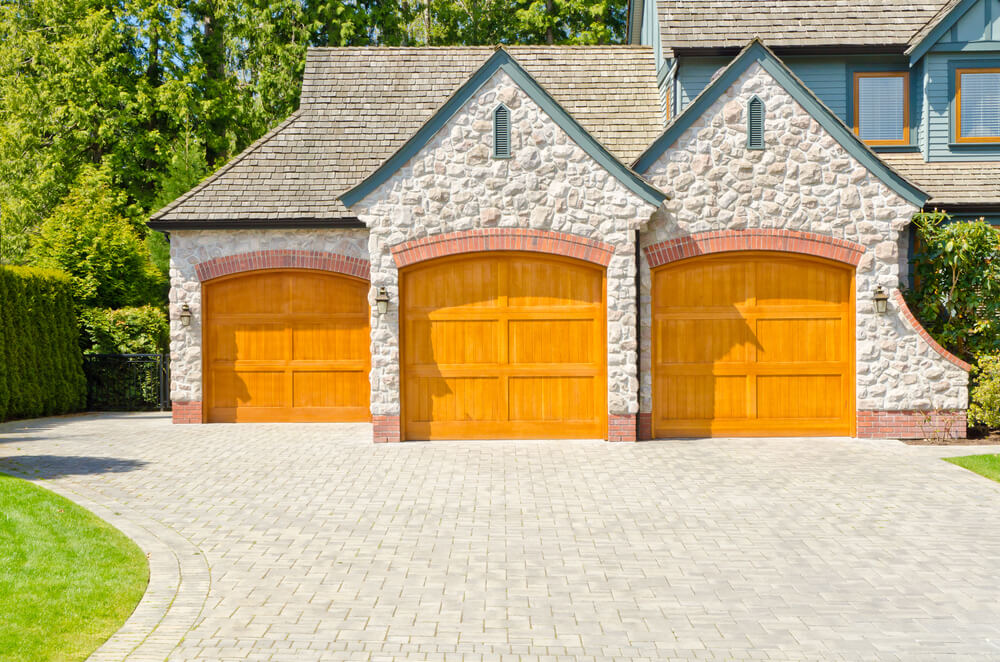 This first three car garage features staggered design, with two of the light natural wood doors up front and a third recessed on the left. Red brick arches frame the doors under stone facade.