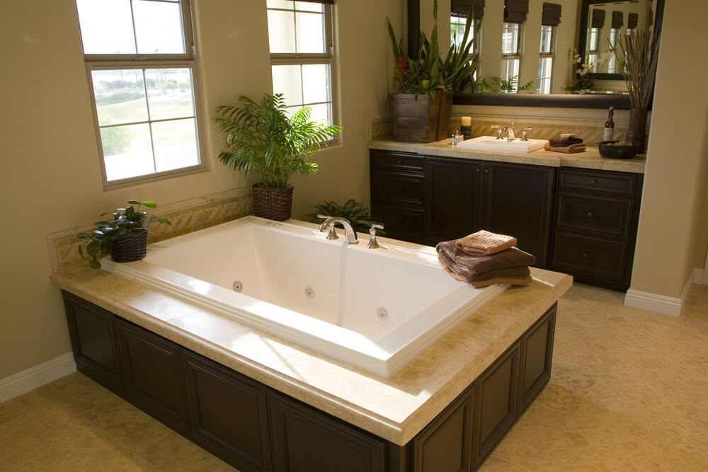 Here's another whirlpool jet equipped soaking tub, seated inside large dark wood, marble topped enclosure over beige tile flooring. Matching vanity and potted plants complete the look.