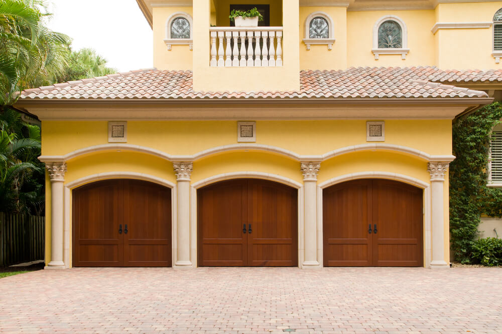 Front-extension garage features yellow facade with white bricks and columns surrounding 3 natural wood carriage style doors.